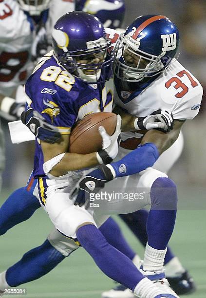 Johnnie Harris of the New York Giants brings down Keenan Howry of the Minnesota Vikings on October 26, 2003 at the Hubert H. Humphrey Metrodome in...