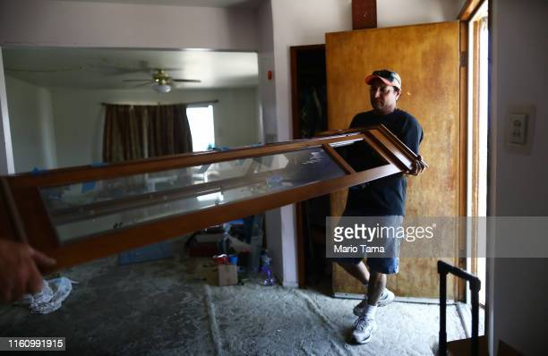 Johnnie Jackson helps remove part of a grandfather clock from the Eldridge family home which has been deemed uninhabitable due to structural damage...