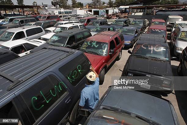 Johnny Bautista paints identifying marks on cars that were turned in through the Cash for Clunkers federal program at Aadlen Brothers Auto Wrecking...