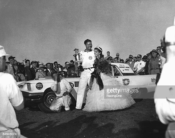 Johnny Beauchamp driver of the Ford stands in victory lane in what he thought was his victory but was actually a victory for Lee Petty after the...