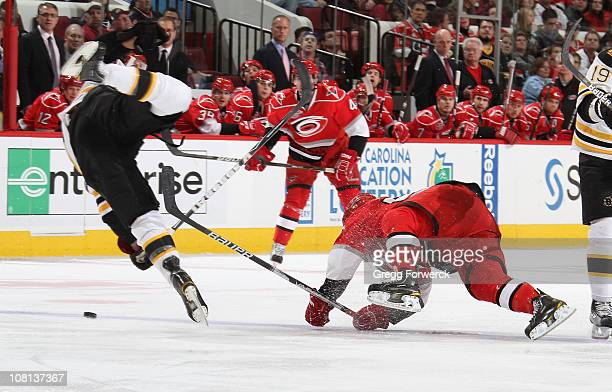 Johnny Boychuk of the Boston Bruins collides with Jeff Skinner of the Carolina Hurricanes during an NHL game on January 18 2011 at RBC Center in...