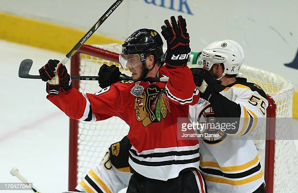 Johnny Boychuk of the Boston Bruins hooks Jonathan Toews of the Chicago Blackhawks around the necxk with his stick during Game One of the 2013 NHL...