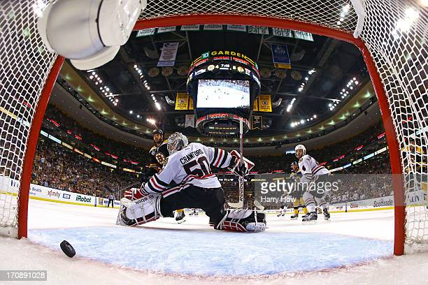 Johnny Boychuk of the Boston Bruins scores a goal against Corey Crawford of the Chicago Blackhawks during the third period in Game Four of the 2013...