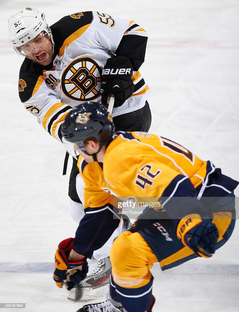 Johnny Boychuk #55 of the Boston Bruins takes a slapshot against Mattias Ekholm #42 of the Nashville Predators at Bridgestone Arena on December 23, 2013 in Nashville, Tennessee.