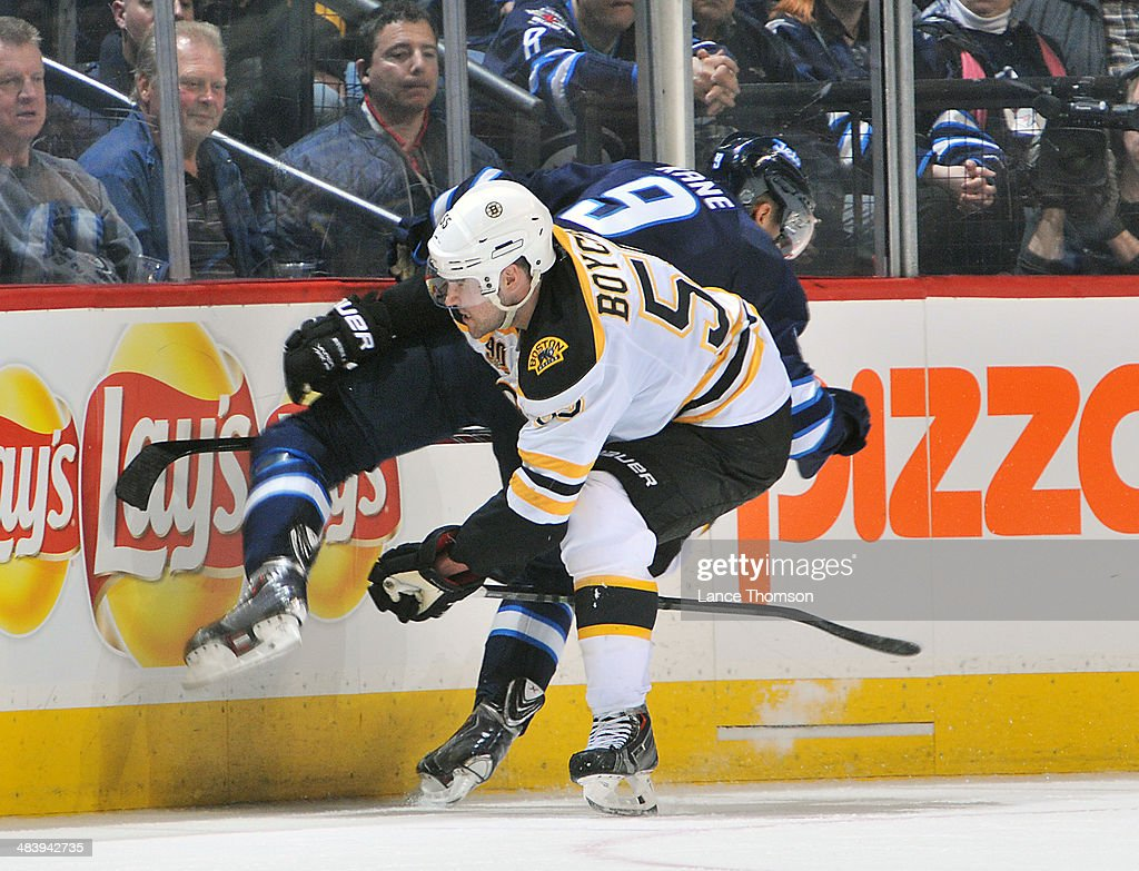 Johnny Boychuk #55 of the Boston Bruins upends Evander Kane #9 of the Winnipeg Jets along the boards during third period action at the MTS Centre on April 10, 2014 in Winnipeg, Manitoba, Canada.