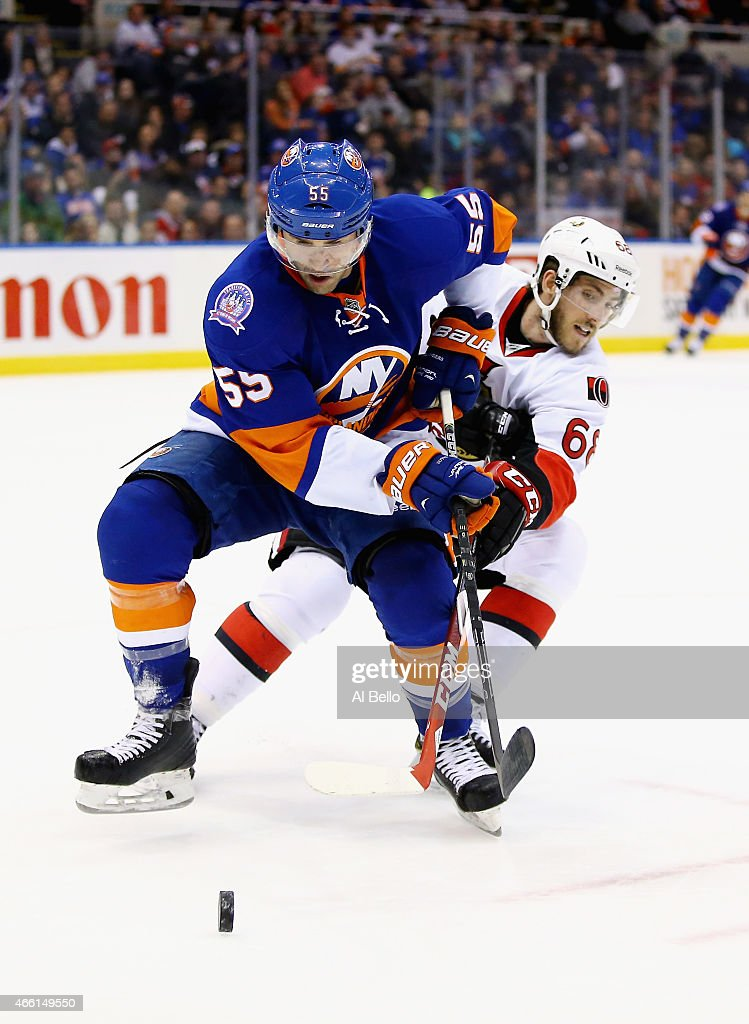 Johnny Boychuk #55 of the New York Islanders and Mike Hoffman #68 of the Ottawa Senators battle for the puck during their game at the Nassau Veterans Memorial Coliseum on March 13, 2015 in Uniondale, New York.