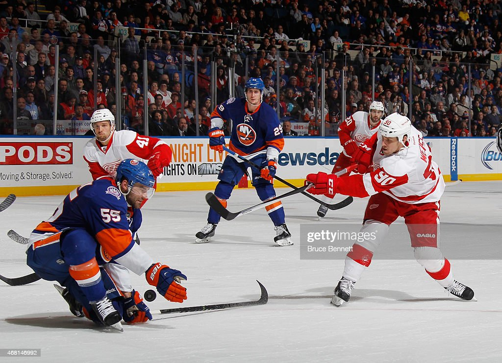 Johnny Boychuk #55 of the New York Islanders blocks a shot by Stephen Weiss #90 of the Detroit Red Wings at the Nassau Veterans Memorial Coliseum on March 29, 2015 in Uniondale, New York. The Islanders defeated the Red Wings 5-4.