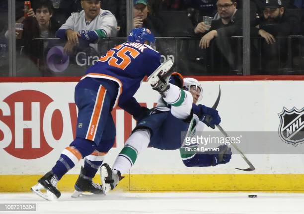 Johnny Boychuk of the New York Islanders checks Markus Granlund of the Vancouver Canucks during the second period at the Barclays Center on November...