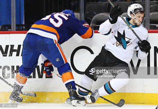 Johnny Boychuk of the New York Islanders checks Melker Karlsson of the San Jose Sharks at Barclays Center on October 21 2017 in the Brooklyn borough...