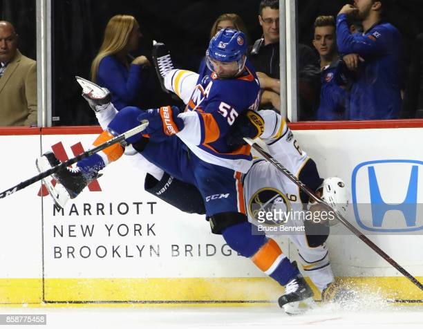 Johnny Boychuk of the New York Islanders hits Evander Kane of the Buffalo Sabres into the boards during the first period at the Barclays Center on...