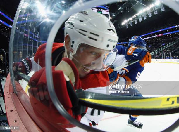 Johnny Boychuk of the New York Islanders hits Jordan Staal of the Carolina Hurricanes into the boards during the first period at the Barclays Center...
