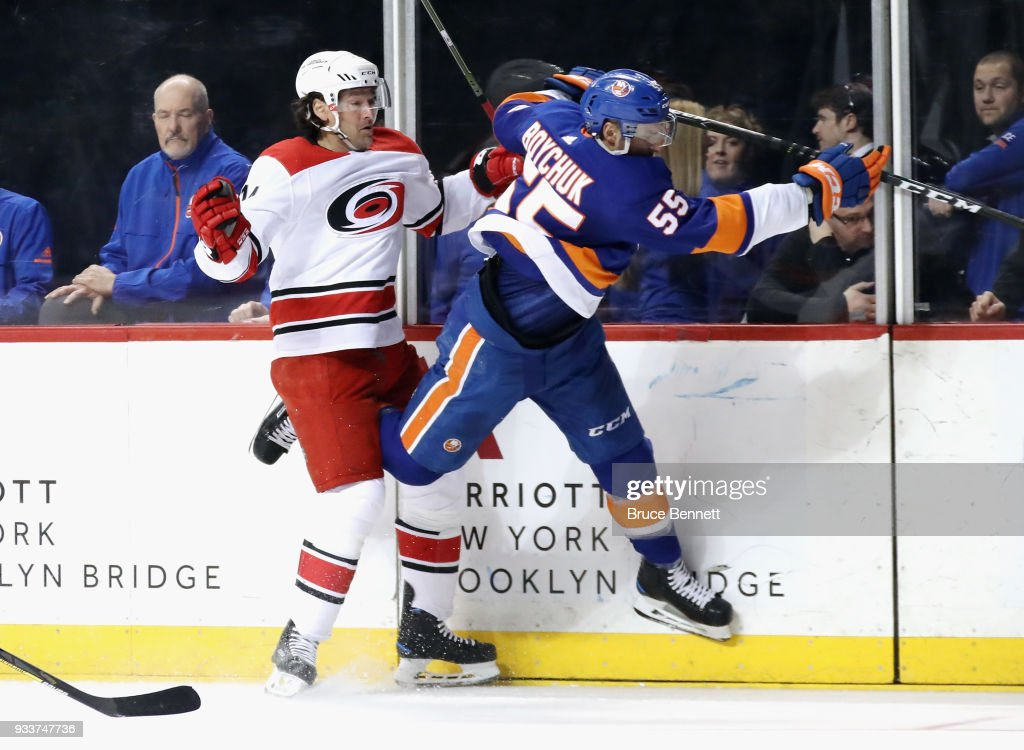 Johnny Boychuk #55 of the New York Islanders hits Justin Williams #14 of the Carolina Hurricanes into the boards during the first period at the Barclays Center on March 18, 2018 in the Brooklyn borough of New York City.