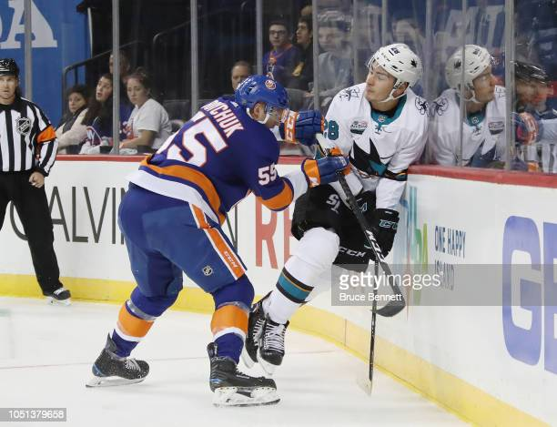 Johnny Boychuk of the New York Islanders hits Timo Meier of the San Jose Sharks into the boards during the first period at the Barclays Center on...