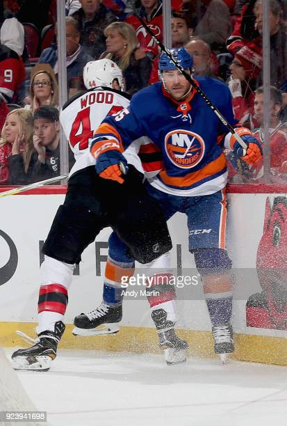 Johnny Boychuk of the New York Islanders is checked into the boards by Miles Wood of the New Jersey Devils during the game at Prudential Center on...