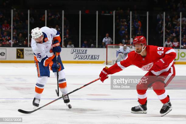 Johnny Boychuk of the New York Islanders takes a shot against Darren Helm of the Detroit Red Wings during the third period at NYCB Live's Nassau...