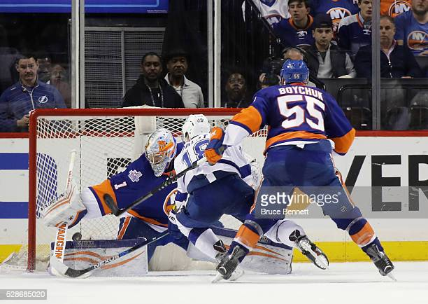 Johnny Boychuk of the New York Islanders takes a two minute penalty for slashing Ondrej Palat of the Tampa Bay Lightning as he gets a shot off...