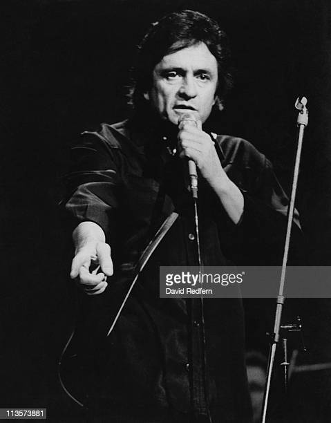Johnny Cash US country singersongwriter singing into a microphone during a live concert performance circa 1970 Cash is pointing with his other hand
