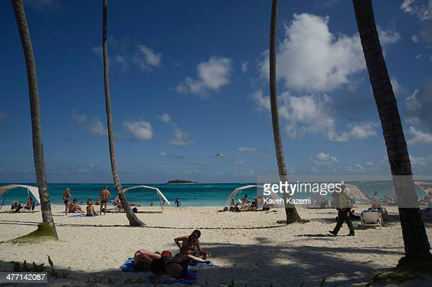 Johnny Cay coral islet is seen in the background of the beach with palm trees where people are spending the day on January 26 2014 in San Andres...