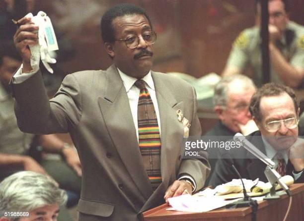 Johnny Cochran lead defense attorney for OJ Simpson holds up golf gloves 16 June as he questions prosecution witness Richard Rubin Rubin testified...