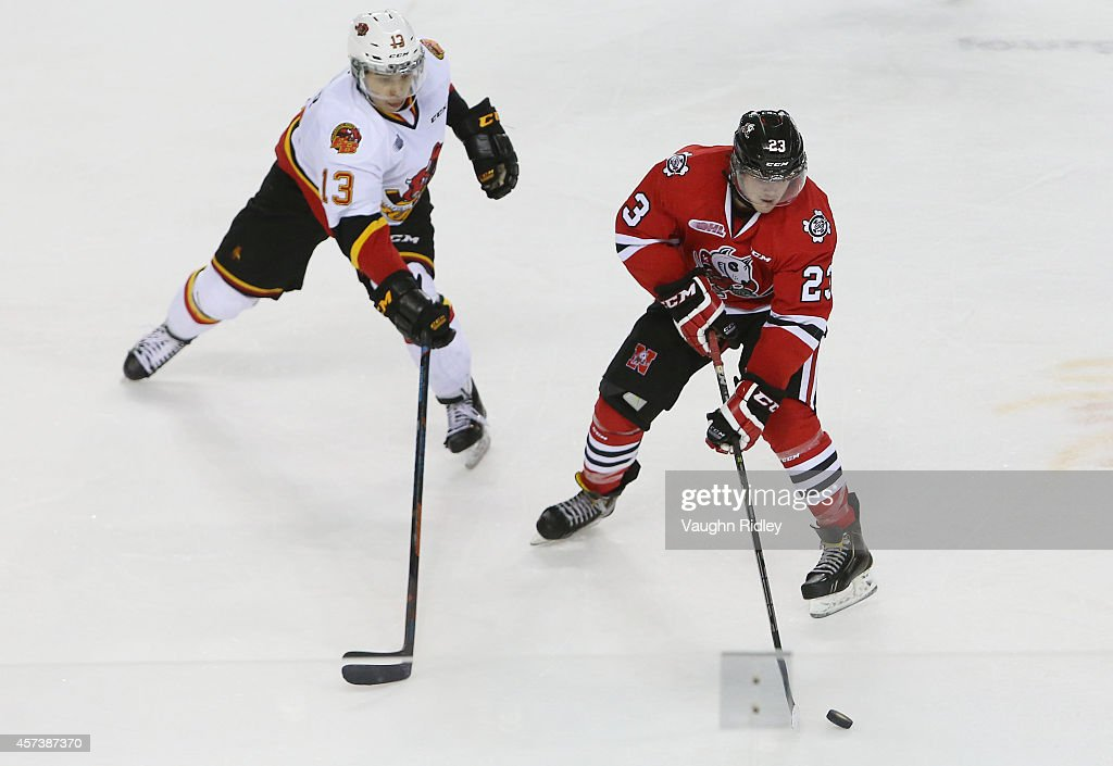 Johnny Corneil #23 of the Niagara Ice Dogs and Stephen Harper #13 of the Belleville Bulls battle for the puck during an OHL game at the Meridian Centre on October 16, 2014 in St Catharines, Ontario, Canada.
