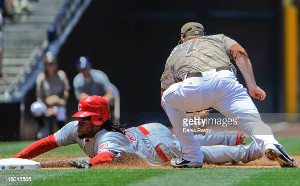 Johnny Cueto of the Cincinnati Reds slides safely into third base ahead of the tag of Chase Headley of the San Diego Padres during the third inning...