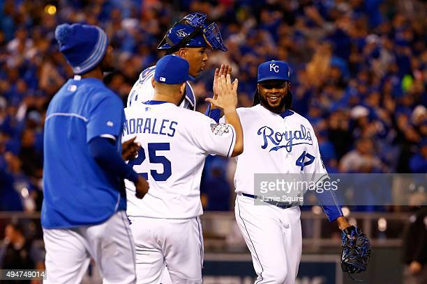 Johnny Cueto of the Kansas City Royals celebrates with Salvador Perez of the Kansas City Royals and Kendrys Morales of the Kansas City Royals after...