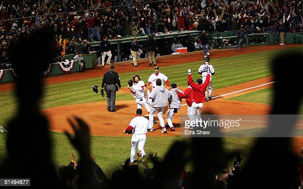 Johnny Damon of the Boston Red Sox celebrates with his teammates after scoring the game winning run on an RBI single by David Ortiz to defeat the New...
