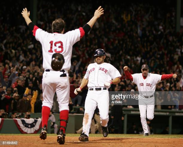 Johnny Damon of the Boston Red Sox celebrates with teammate Doug Mientkiewicz after scoring the game winning run on a single hit by David Ortiz in...