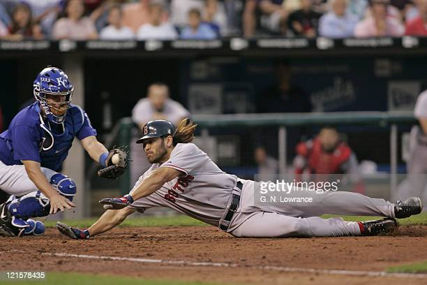 Johnny Damon of the Boston Red Sox slides in to score ahead of the tag during a game against the Kansas City Royals at Kauffman Stadium in Kansas...