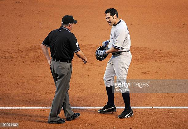 Johnny Damon of the New York Yankees argues a call with first base umpire Dale Scott at the end of the third inning in Game Five of the ALCS against...