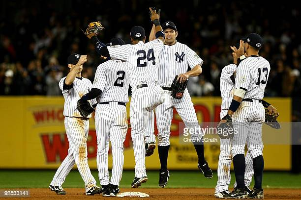 Johnny Damon of the New York Yankees celebrates with Robinson Cano and Alex Rodriguez after defeating the Philadelphia Phillies two win Game Two of...