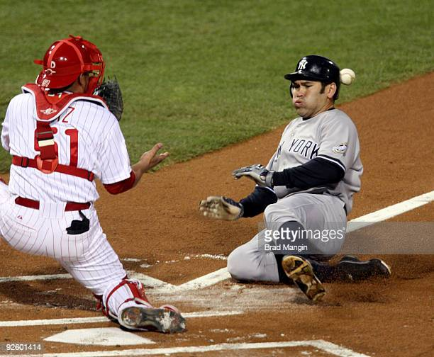 Johnny Damon of the New York Yankees gets hit by the ball as he slides safely into home on a sacrifice fly by Jorge Posada ahead of the throw to...