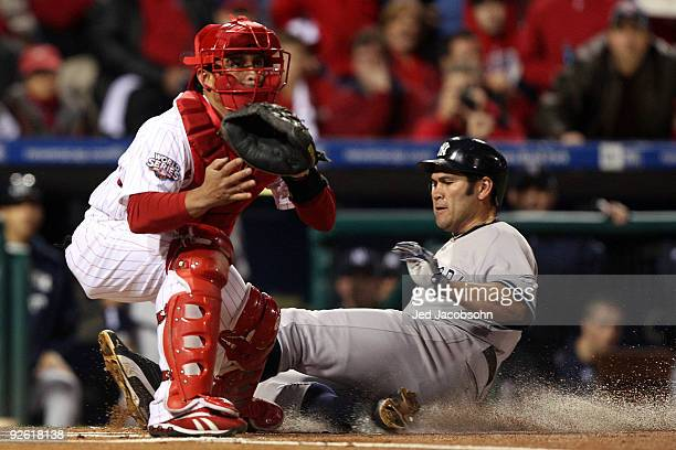 Johnny Damon of the New York Yankees slides into home plate as he scores on a RBI double by Alex Rodriguez in the top of the first inning against...