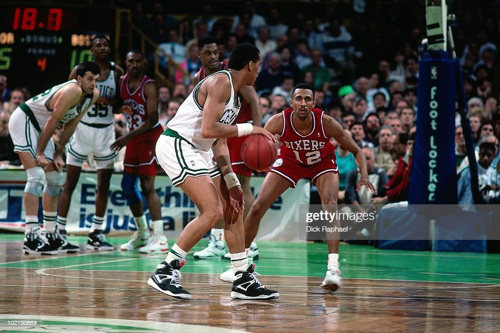 Johnny Dawkins #12 of the Philadelphia 76ers defends against Dennis Johnson #3 of the Boston Celtics during a game played in 1990 at the Boston Garden in Boston, Massachusetts.
