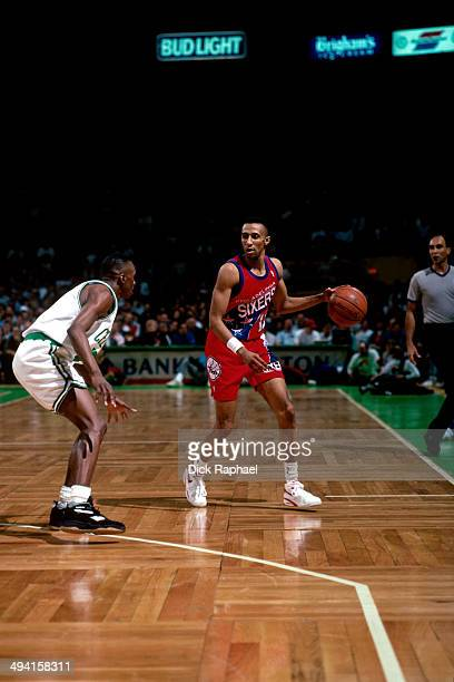 Johnny Dawkins of the Philadelphia 76ers handles the ball against Dee Brown of the Boston Celtics during a game played at the Boston Garden in Boston...
