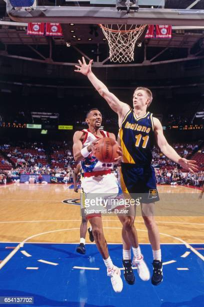 Johnny Dawkins of the Philadelphia 76ers shoots against Detlef Schrempf of the Indiana Pacers during a game played circa 1993 at the Spectrum in...