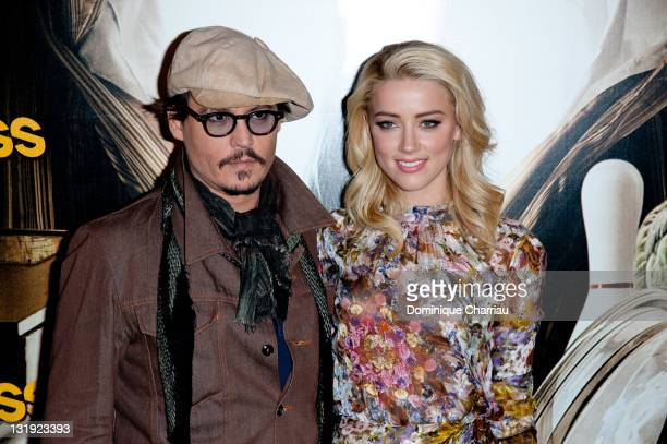 Johnny Depp and Amber Heard pose during the 'Rhum Express' Photocall at Hotel Paris Plaza Athenee on November 8 2011 in Paris France
