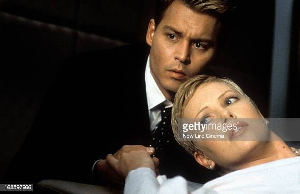 Johnny Depp holding Charlize Theron's hands in a scene from the film 'The Astronaut's Wife' 1999