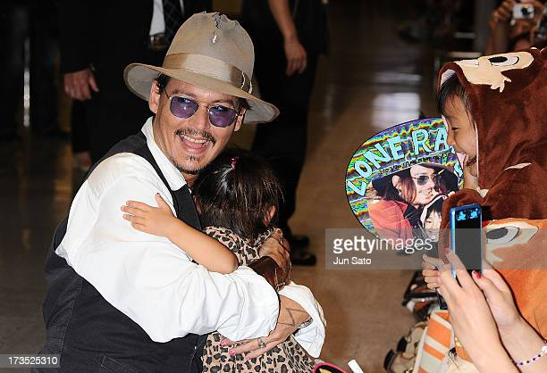 Johnny Depp is greeted by a young fan as he arrives at Narita International Airport on July 16 2013 in Narita Japan