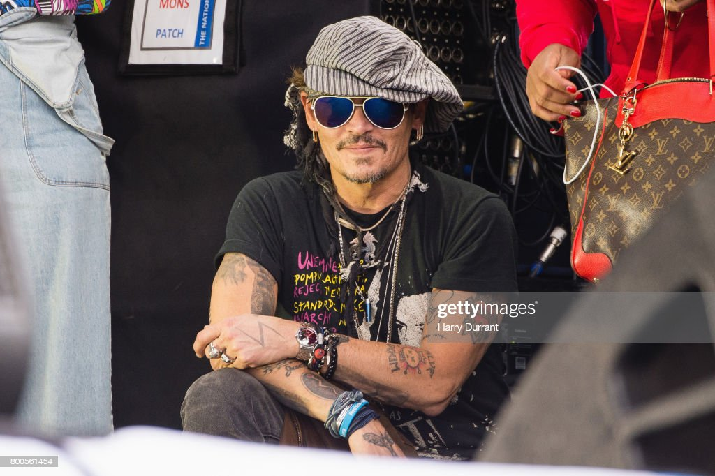 Johnny Depp sits at the side of the Pyramid Stage watching 'Run The Jewels' perform on day 3 of the Glastonbury Festival 2017 at Worthy Farm, Pilton on June 24, 2017 in Glastonbury, England.