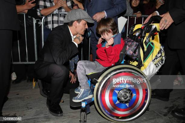 Johnny Depp talks to a child in a wheelchair at the 'Richard Says Goodbye' premiere during the 14th Zurich Film Festival at Festival Centre on...