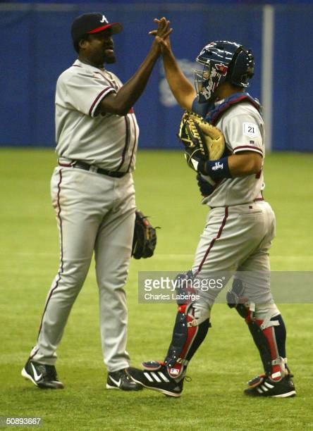 Johnny Estrada of the Atlanta Braves and teammate Antonio Alfonseca celebrate after recording the final out in the Braves' 50 win against the...