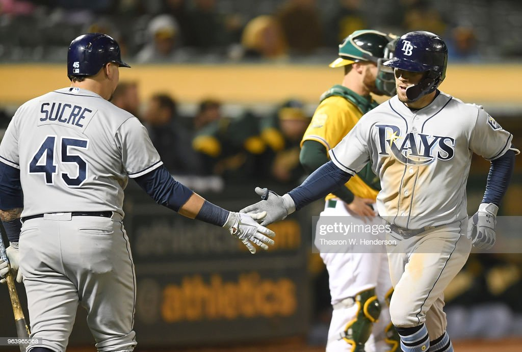 Johnny Field #10 of the Tampa Bay Rays is congratulated by Jesus Sucre #45 after Field hit a solo home run against the Oakland Athletics in the top of the eighth inning at the Oakland Alameda Coliseum on May 30, 2018 in Oakland, California. The Rays won the game 6-0.