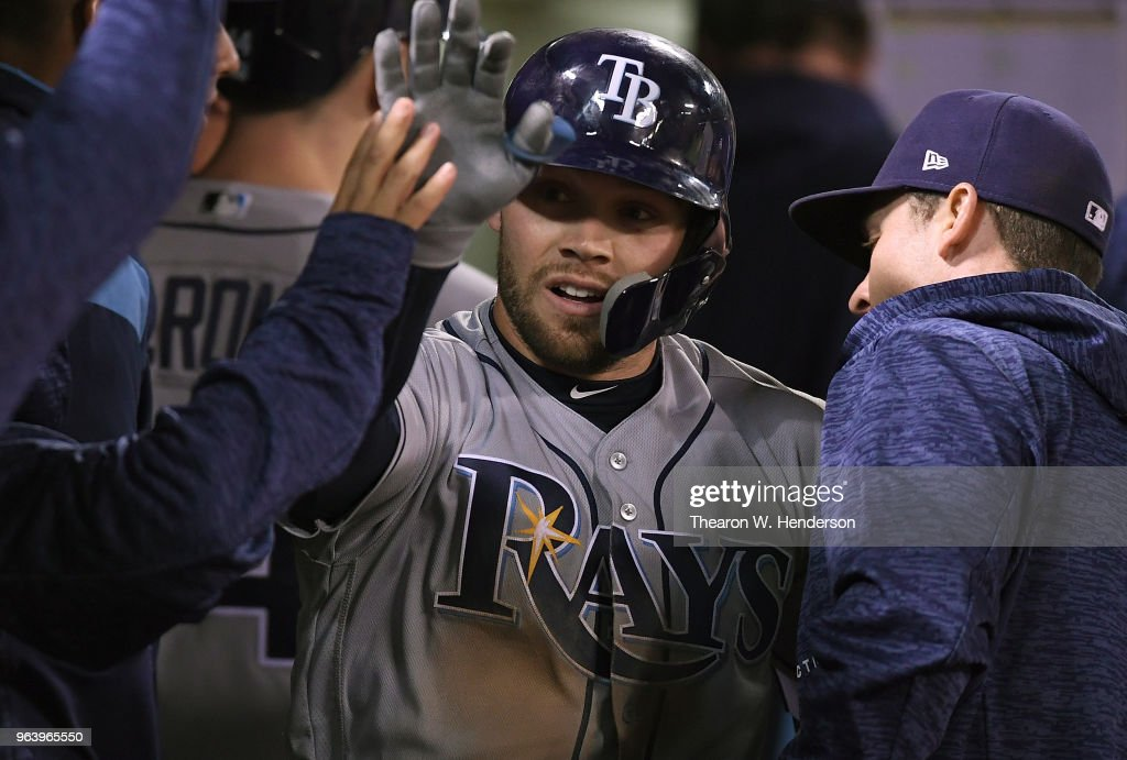Johnny Field #10 of the Tampa Bay Rays is congratulated by teammates after he hit a solo home run against the Oakland Athletics in the top of the eighth inning at the Oakland Alameda Coliseum on May 30, 2018 in Oakland, California. The Rays won the game 6-0.