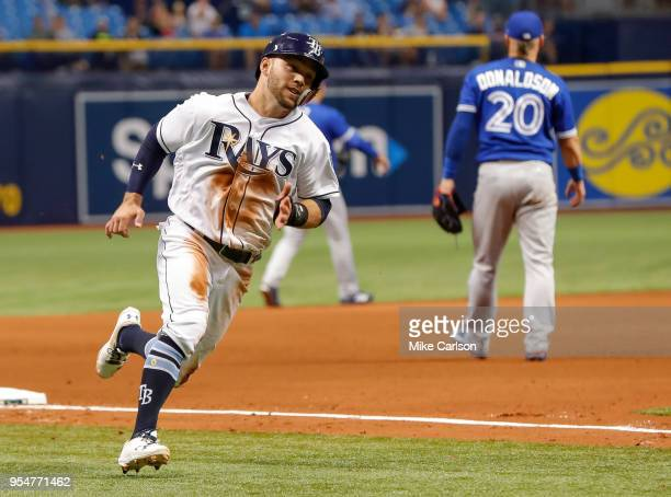 Johnny Field of the Tampa Bay Rays rounds the bases to score as Josh Donaldson of the Toronto Blue Jays looks for a late throw in the seventh inning...