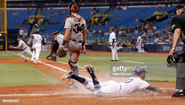 Johnny Field of the Tampa Bay Rays scores as catcher James McCann of the Detroit Tigers watches Carlos Gomez reach base safely on the suicide squeeze...
