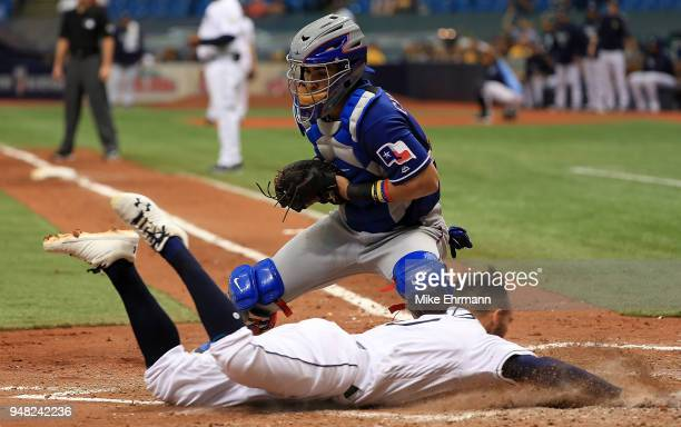 Johnny Field of the Tampa Bay Rays scores in front of the tag from Robinson Chirinos of the Texas Rangers during a game at Tropicana Field on April...
