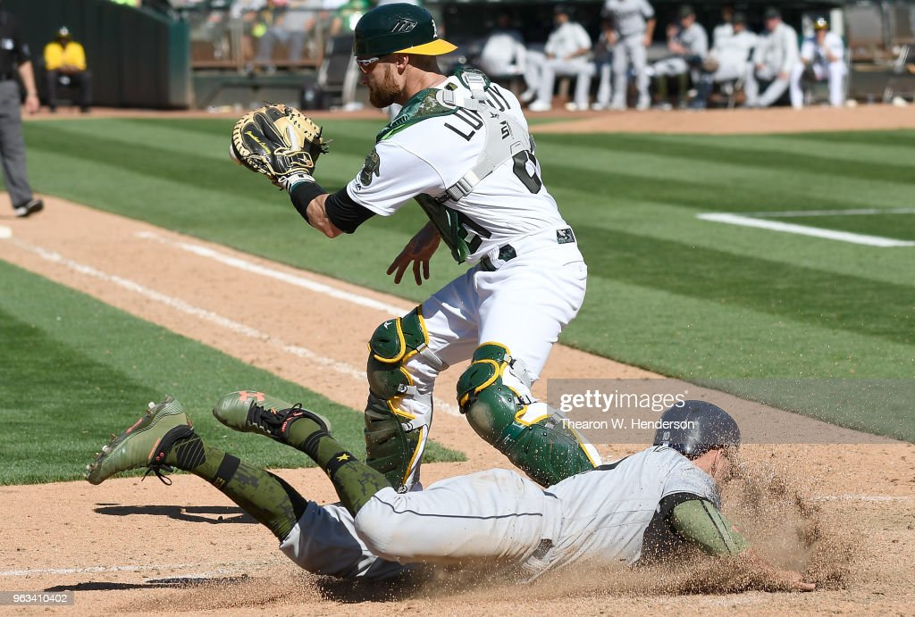 Johnny Field #10 of the Tampa Bay Rays scores sliding home before the throw to Jonathan Lucroy #21 of the Oakland Athletics in the top of the 13th inning at the Oakland Alameda Coliseum on May 28, 2018 in Oakland, California. The Rays won the game 1-0.