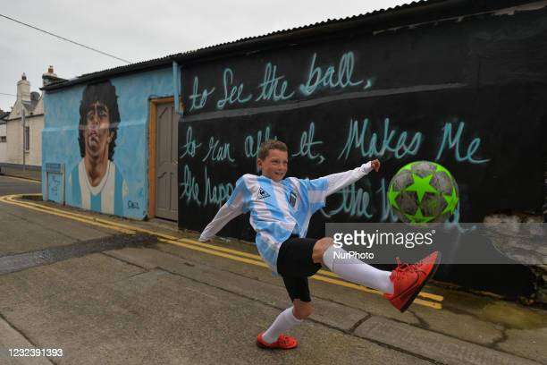 Johnny Figo Murphy, age 9, showing off his soccer skils in front of a new mural by CHELS , representing Diego Maradona, one of the greatest players...