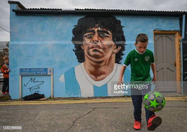 Johnny Figo Murphy, age 9, shows off his soccer skils in front of a new mural by CHELS , representing Diego Maradona, one of the greatest players in...